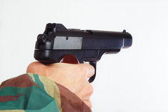 Hand in camouflage uniform with a semi-automatic army gun close up Royalty Free Stock Photo