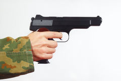 Hand in camouflage uniform with a semi-automatic gun on white background Royalty Free Stock Images