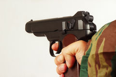 Hand in camouflage uniform with semi-automatic pistol Royalty Free Stock Image