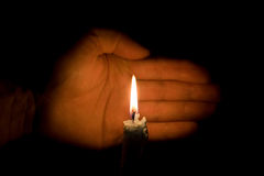 Hand and a candle. Burning in the dark Stock Image
