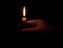 Hand with candle in darkness Royalty Free Stock Photos