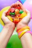 Hand and candy. Woman's hand s offering a handful of colorful jelly candies over balloons in a party concept Stock Images