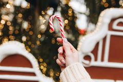 Hand with candy on blur holdiay background Stock Photos