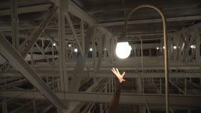 Hand cannot reach light bulbs.  stock footage