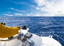Hand of captain on steering wheel of motor boat in the blue ocean during the fishery day. Success fishing concept. Ocean yacht. Hand of captain on steering royalty free stock images