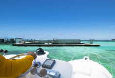 Hand of captain on steering wheel of motor boat in the blue ocean during the fishery day. Success fishing concept. Ocean yacht. Hand of captain on steering royalty free stock image