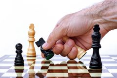 Hand capturing chess piece Stock Photography