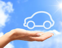 Hand with car. Against blue sky background