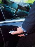Hand on a car door. Businessman's hand opening door of his luxury car Royalty Free Stock Photo