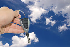 Hand with car key. In front of blue sky Stock Photography