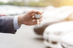 Hand with car key. Close up hand holding car key, many automobile at the background Stock Photo