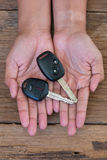 Hand with a car key on wood background. Hand with a car key on old wood background Royalty Free Stock Image