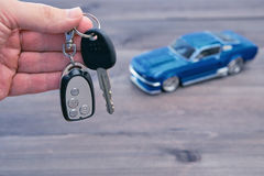 Hand with car keys and small car model. Hand with car keys and small toy car model blurred on background. concept image for rent or buy a car Stock Image