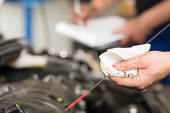 Hand of car mechanic checking oil Royalty Free Stock Photos