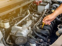 Hand of car mechanic working in auto repair service. He have fix old car engine streaked with dust and oil stains.  Royalty Free Stock Image