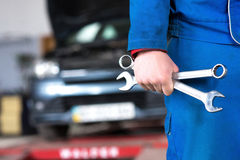 Hand of car mechanic with wrench. Auto repair garage Stock Images