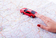 Hand with a car and road map. Toy red car on female hand on white background Stock Photography