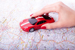 Hand with a car and road map. Toy red car on female hand on white background Royalty Free Stock Photo