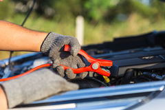 Hand of car technician holding cable to connect to battery Stock Photos