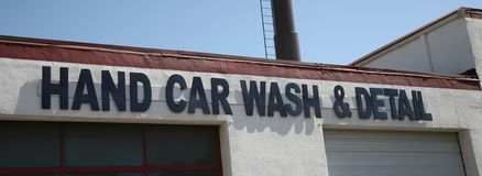 Hand Car wash and Detail. A car wash shop where automobiles are washed and detailed by hand without the use of equipment or automated machines Royalty Free Stock Image