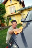 Hand car wash. Male cleaning his car using sponge and foam. Hand car wash. Smiling male his cleaning car using sponge and foam in the house yard Royalty Free Stock Images