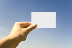 Hand Card. White card in a hand against the blue sky Royalty Free Stock Image
