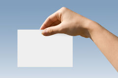 Hand Card. White card in a hand against the blue sky Royalty Free Stock Photo