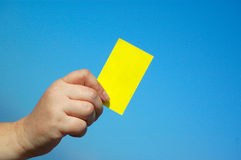 Hand with card. A white hand of a caucasian woman showing a yellow blank business card in front of blue sky background Royalty Free Stock Photos
