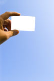 Hand and card on blue sky Royalty Free Stock Image
