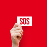 In the hand card with the inscription sos . In the hand card with the inscription sos on a red background Royalty Free Stock Photo