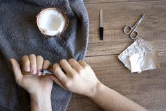 Hand care, folk hand care. Manicure with coconut oil, manicure tools: scissors, nail file. Foil Gel Polish Remover. Beauty and spa stock images