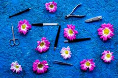 Hand care. Set of manicure tools and flowers on blue background top view Royalty Free Stock Photography