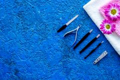 Hand care. Set of manicure tools and flowers on blue background top view copyspace Stock Photo