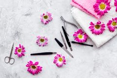 Hand care. Set of manicure tools, towels and flowers on grey background top view copyspace Stock Image