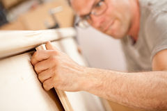 Hand of a carpenter building. Focus on the robust hand of a carpenter holding a flap (a wooden board) he's placing on a piece of a handcrafted wooden piece of Stock Images