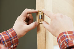 Hand of carpenter at lock installation Royalty Free Stock Photo