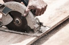 Hand of a carpenter using a circular saw to cut a wooden plank. Tool used to saw wood. Carpentry tool. Electric saw, circular blade stock photography