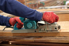 Hand of carpenter using electric planer with wooden plank in carpentry workshop Stock Photo