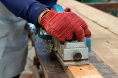 Hand of carpenter using electric planer with wooden plank in carpentry workshop Stock Images