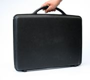 Hand carries attache case. Female hand holds black attache case against white background Stock Image