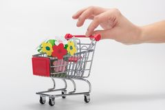 Hand carries a grocery cart with a children`s crafts bouquet of flowers stock image