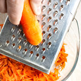 The hand with carrot rubs. Into glass bowl Royalty Free Stock Images