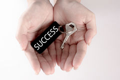 The hand carry the silver key with the label of success wording. Key to success concept isolated in white background Royalty Free Stock Images