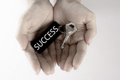 The hand carry the silver key with the label of success wording. Key to success concept  in white background Royalty Free Stock Images