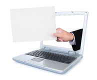 Hand carrying blank paper out of a laptop screen Stock Images