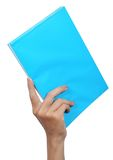 Hand carrying a blue book. Female hand carrying a blue book isolated on white background Royalty Free Stock Photos