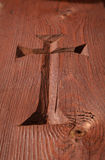 Hand carved cross in brown church door Royalty Free Stock Images