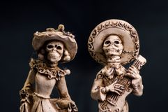 Hand carved skeleton Mexican wedding cake toppers. Mexican skeleton mariachi cake toppers hand carved carved from bone. Flowers on dress and hat. Male holding a royalty free stock image