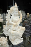The hand-carved stone statue of the Hindu Goddess of Learning, Dewi Saraswati, plays the sitar Stock Image