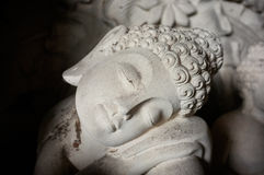 A hand-carved stone statue of a reclining Buddha in Ubud, Bali, Indonesia Stock Photos